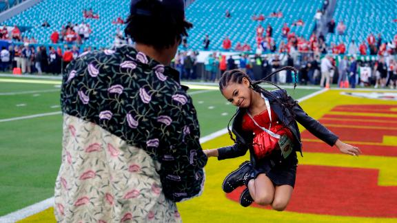 Rapper Jay-Z watches his daughter, Blue Ivy, leap on the field before the game.