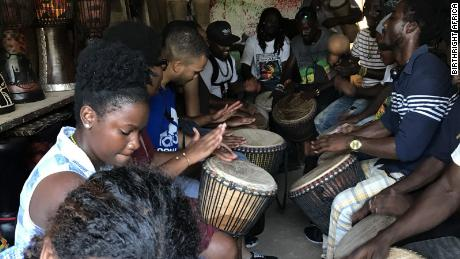 Scholars drumming with artisans from the Arts Centre Market in Accra, Ghana.