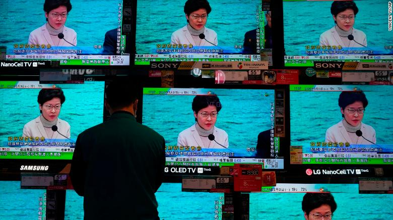 A man stands in front of TV screens broadcasting a speech by Hong Kong Chief Executive Carrie Lam on February 3. Lam said the city would shut almost all border-control points to the mainland.