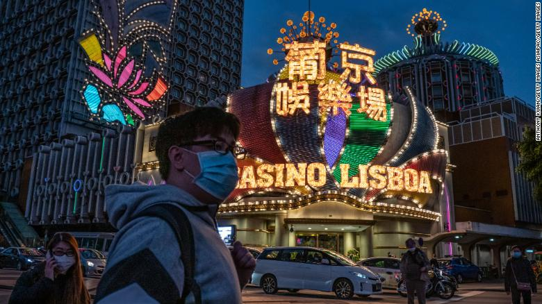 People wearing face masks walk in front of the Grand Lisboa Hotel on January 28, 2020 in Macao.