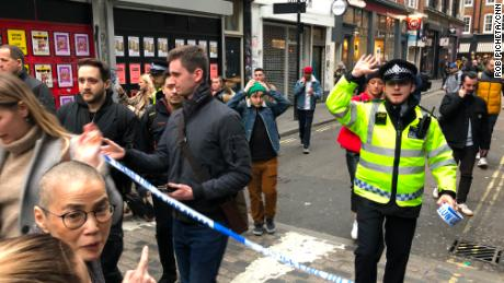 Police leave a cordoned off area in Soho on Monday.