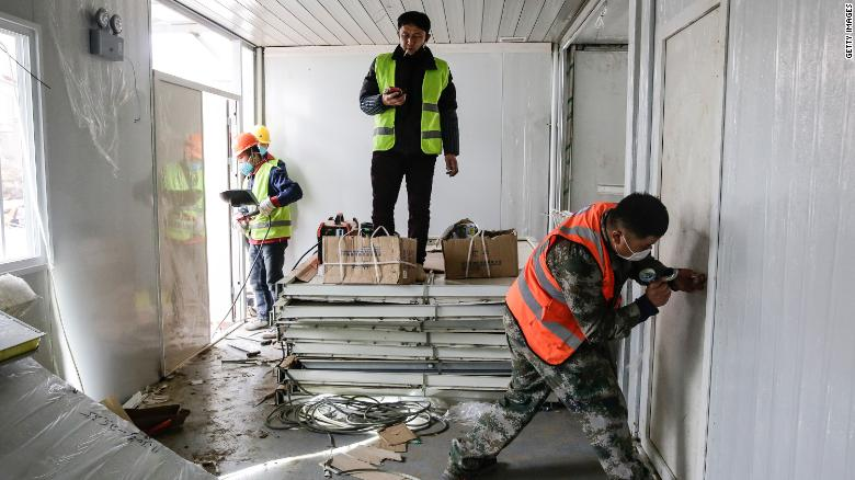Workers pictured near the end of the 10-day contruction period for Huoshenshan Hospital.