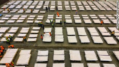 "Workers set up beds at an exhibition centre that was converted into a ""Fangcang hospital"" in Wuhan on February 4."