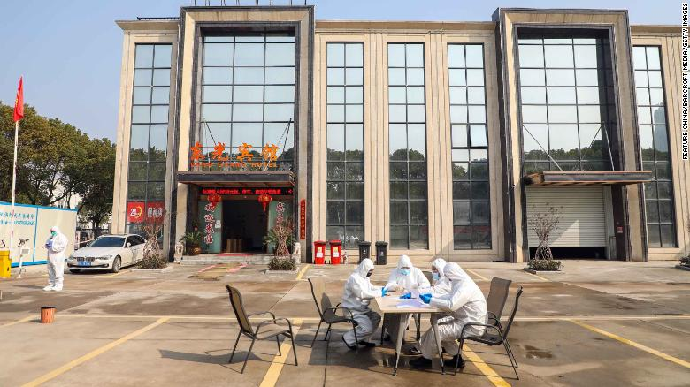 People wearing protective overalls talk outside a Wuhan hotel housing people in isolation on Monday, February 3.