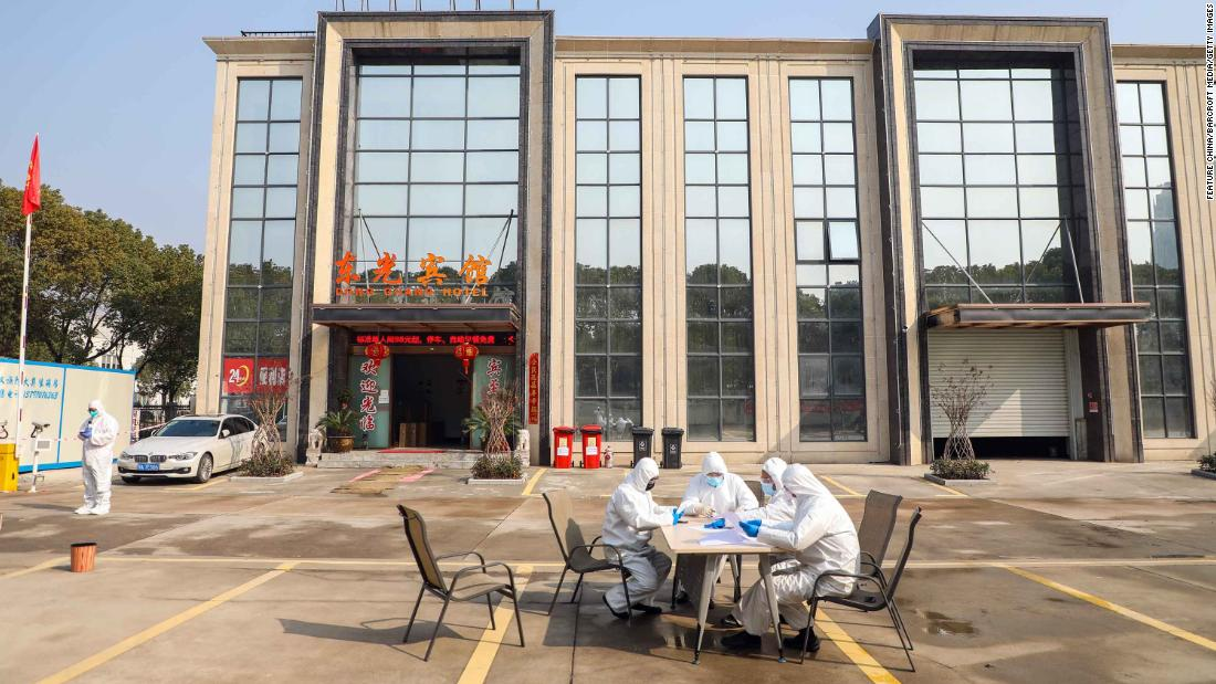People wearing protective overalls talk outside a Wuhan hotel housing people in isolation on February 3.