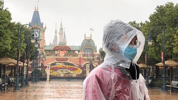 A Disney employee stands in front of the gates of the Shanghai Disney Resort.