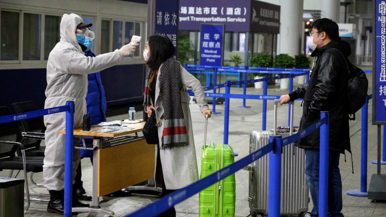A security personnel checks the temperature of passengers arriving at the Shanghai Pudong International Airport in Shanghai on February 4, 2020.