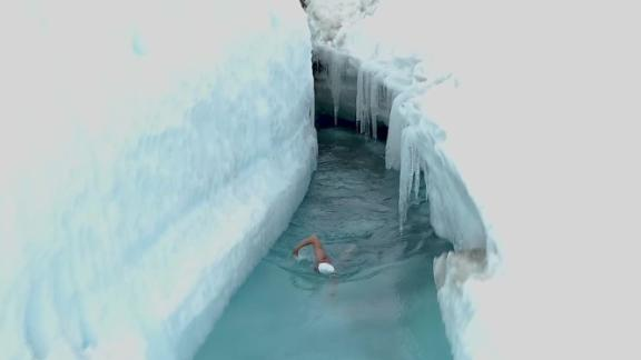 man swims through glacier lake