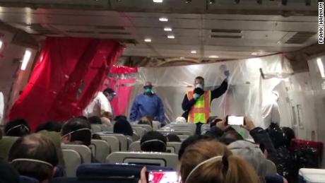 A man makes an announcement aboard the evacuation flight that Frank Hannum and other US citizens were on Wednesday.