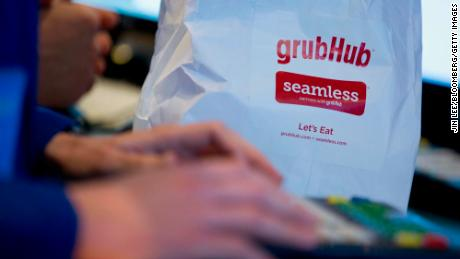 A trader works next to a Grubhub Inc. paper bag on the floor of the New York Stock Exchange (NYSE) in New York, U.S., on Friday, April 4, 2014. GrubHub Inc., which lets hungry city dwellers order food online, raised a higher-than-expected $192 million in an initial public offering, after pricing the shares above a marketed range. Photographer: Jin Lee/Bloomberg via Getty Images