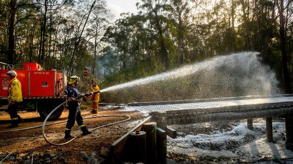 A firefighter coats a bridge with foam as a bushfire burns near Moruya, Australia, on Saturday, January 25.