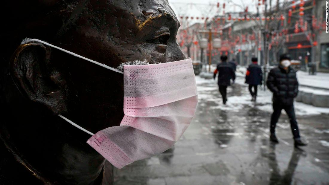 A mask is seen on a statue in Beijing on February 5.