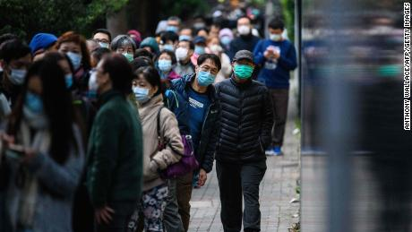 People wearing face masks as a preventative measure following a coronavirus outbreak which began in the Chinese city of Wuhan, line up to purchase face masks in Hong Kong on February 5, 2020.