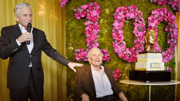 Douglas looks on as his son Michael makes a speech at his 100th birthday party in 2016.