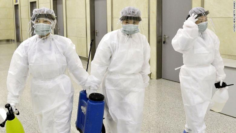 Quarantine staff in protective gear are pictured at Pyongyang International Airport on Saturday.