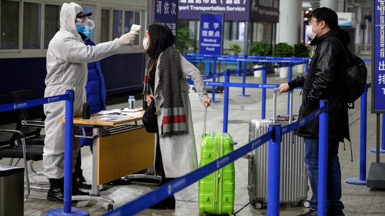 Security personnel check the temperature of passengers arriving at the Shanghai Pudong International Airport on February 4.