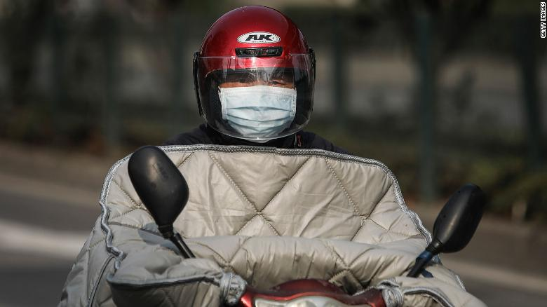 A resident wears a protective mask while riding a scooter on February 5, 2020, in Wuhan.