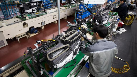 Employees assemble vehicle dashboard modules on a production line at the Hyundai Mobis Co. factory in Asan, South Chungcheong, South Korea, on Tuesday, Jan. 24, 2017. Photo by SeongJoon Cho/Bloomberg/Getty Images