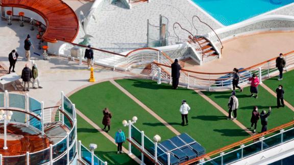 Passengers are seen on the deck of the Diamond Princess cruise ship, docked at the Yokohama Port on February 7.