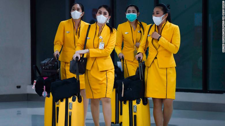 Flight attendants wearing face masks make their way through Don Mueang Airport in Bangkok, Thailand, on February 7.