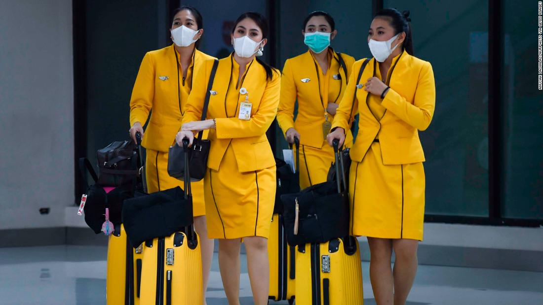 Flight attendants wearing face masks make their way through Don Mueang Airport in Bangkok on February 7.