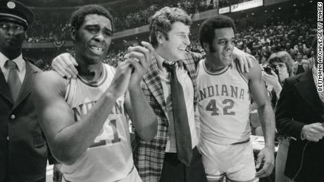 Indiana coach Bobby Knight, center, is walked off the court in jubilation by a tearful Quinn Buckner, left, and Scott May after the Hoosiers won the 1976 NCAA championships in Philadelphia.