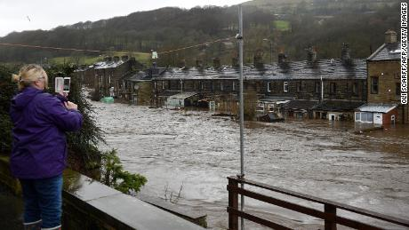 A woman photographs flooded houses in Mytholmroyd, northern England  after the River Calder burst its banks.