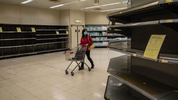 """A shopper walks past empty shelves at a grocery store in Hong Kong on February 9. China's Ministry of Commerce <a href=""""https://www.cnn.com/2020/02/06/asia/wuhan-coronavirus-update-intl-hnk/index.html"""" target=""""_blank"""">encouraged supermarkets and grocery stores</a> to resume operations as the country's voluntary or mandatory quarantines began to take an economic toll."""