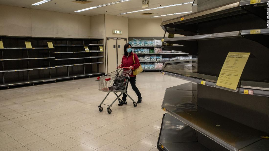 "A shopper walks past empty shelves at a grocery store in Hong Kong on February 9. China's Ministry of Commerce <a href=""https://www.cnn.com/2020/02/06/asia/wuhan-coronavirus-update-intl-hnk/index.html"" target=""_blank"">encouraged supermarkets and grocery stores</a> to resume operations as the country's voluntary or mandatory quarantines began to take an economic toll."