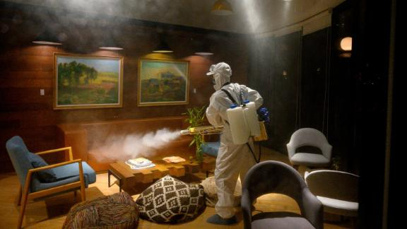 A worker wearing a protective suit uses a machine to disinfect a business establishment in Shanghai, China, on February 9.