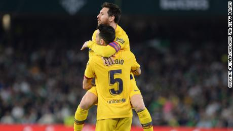 Sergio Busquets holds Messi aloft after equalizing for Barcelona.