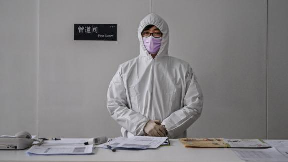 """A worker wears a protective suit as he waits to screen people entering an office building in Beijing on February 10. China's workforce is <a href=""""https://edition.cnn.com/2020/02/10/business/china-companies-return-to-work-coronavirus/index.html"""" target=""""_blank"""">slowly coming back to work</a> after the coronavirus outbreak forced many parts of the country to extend the Lunar New Year holiday by more than a week."""