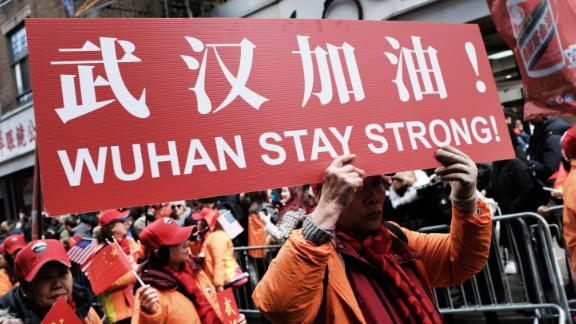 """People participating in a Lunar New Year Parade in New York City hold signs reading, """"Wuhan stay strong!"""" on February 9."""