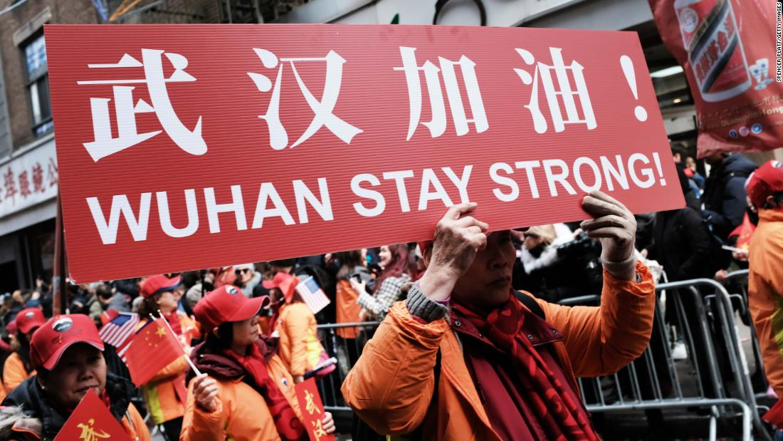 "People participating in a Lunar New Year Parade in New York City hold signs reading, ""Wuhan stay strong!"" on February 9."