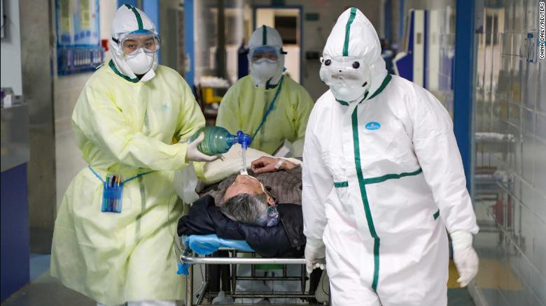 Medical workers in protective suits move a patient at an isolated ward of a hospital in Wuhan on February 6.