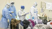 Medical staff check a patient's condition at a temporarily converted hospital for coronavirus patients in Wuhan.