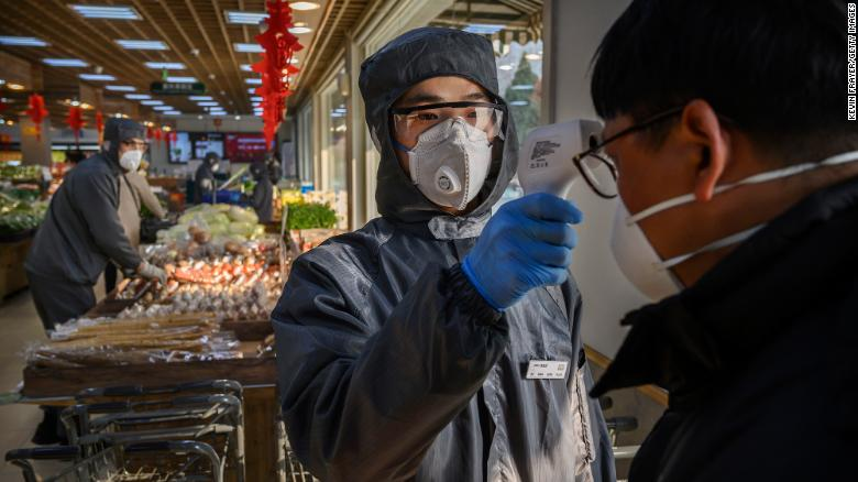 A supermarket worker checks the temperature of a customer in Beijing on Tuesday, February 11.