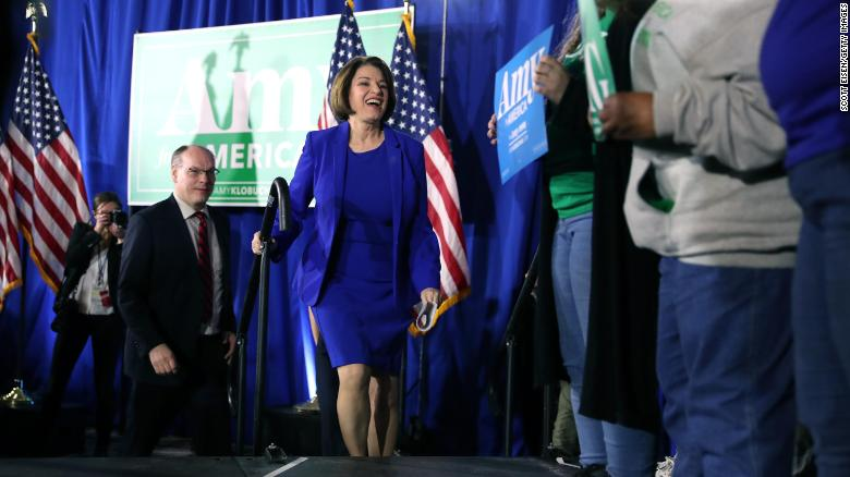 Klobuchar takes the stage with spouse John Bessler during a primary night event at the Grappone Conference Center on February 11, 2020 in Concord, New Hampshire.