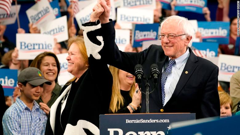 Sanders holds the hand of his spouse Jane O'Meara Sanders as he takes the stage during a primary night event on February 11, 2020 in Manchester, New Hampshire.