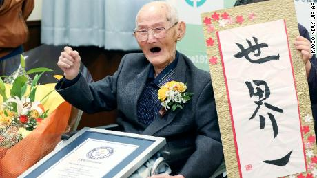 Chitetsu Watanabe, 112, poses next to the calligraphy he wrote after being awarded as the world's oldest living male by Guinness World Records.