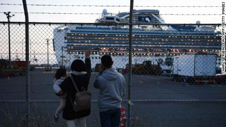 Relatives of passengers wave to the Diamond Princess cruise ship, which has around 3,600 people quarantined onboard due to fears of the new coronavirus.