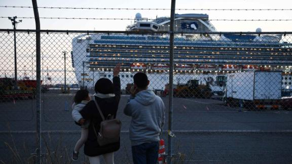 """Relatives of quarantined passengers wave at the Diamond Princess cruise ship as it leaves a port in Yokohama, Japan, to dump wastewater and generate potable water. Dozens of people on the ship <a href=""""https://www.cnn.com/2020/02/10/us/coronavirus-cruise-ship-americans-quarantine/index.html"""" target=""""_blank"""">were infected with coronavirus.</a>"""
