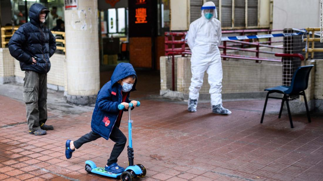 A child rides a scooter past a police officer wearing protective gear outside the Hong Mei House in Hong Kong on February 11. More than 100 people evacuated the housing block after four residents in two different apartments tested positive for the coronavirus.