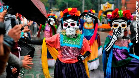 Colorfully costumed participants march in a Día de los Muertos parade along Reforma Avenue in Mexico City on October 27, 2019.