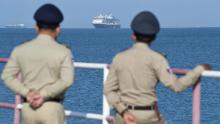 Authorities watch as the Westerdam cruise ship approaches a port in Sihanoukville, Cambodia, on Thursday, February 13. Despite having no confirmed cases of coronavirus on board, the Westerdam was refused port by four other Asian countries before being allowed to dock in Cambodia.