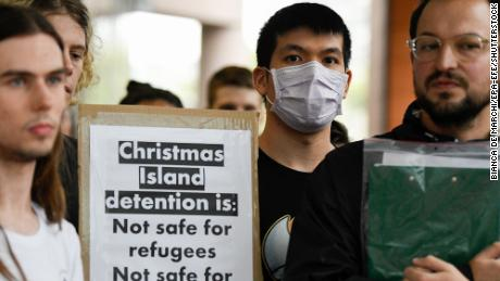 Protesters hold placards during a rally against an inbound travel ban on foreign travellers from China in Sydney on February 7, 2020.