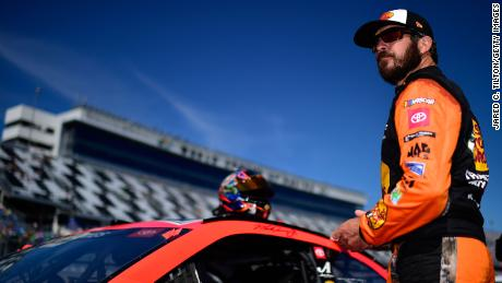 Martin Truex Jr., driver of the #19 Bass Pros Shops Toyota, stands on the grid during qualifying for the NASCAR Cup Series 62nd annual Daytona 500.