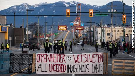 Police officers stand on a road after clearing the intersection of protesters that were blocking an entrance to a port Wednesday in Vancouver, British Columia. The demonstration expressed solidarity with Wet'suwet'en protesters who were arrested last week.