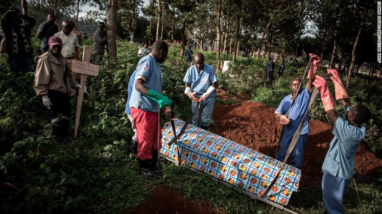 Health workers prepare to bury a coffin containing a victim of the ebola virus on May 16, 2019 in Butembo.