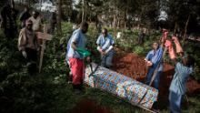 Health workers prepare to bury a coffin containing the body of an Ebola victim on May 16, 2019 in Butembo, DRC.
